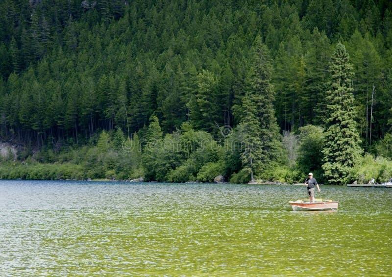 Visser in zijn boot op het whiteswan meer royalty-vrije stock foto's