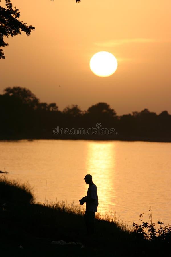 Visserij bij zonsondergang stock afbeelding