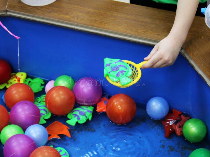 Visserij in de paddelende pool Kinderen` s speelgoed in de pool stock foto's