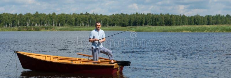 Visserij door van een boot op de rivier te spinnen stock fotografie