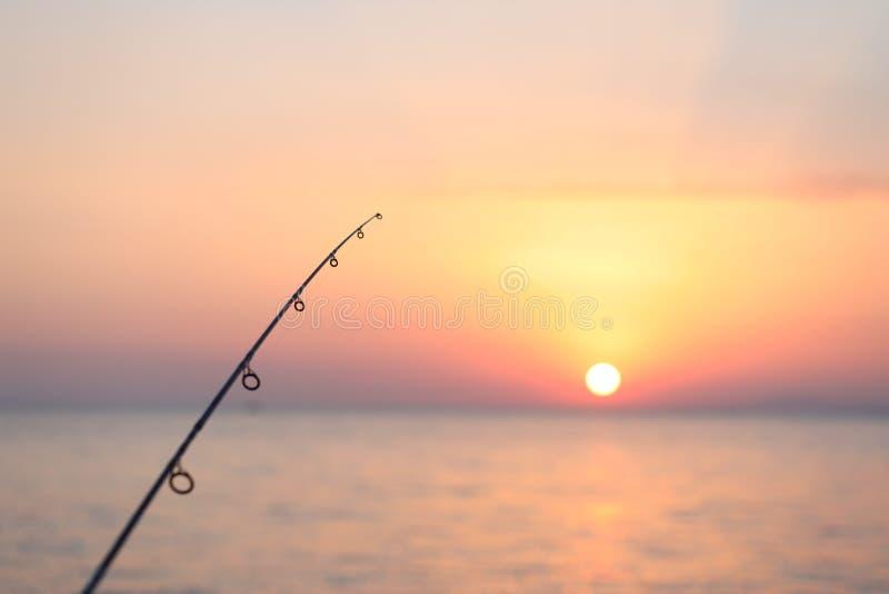 Visserij in het overzees in zonsondergang op de horizon royalty-vrije stock afbeelding
