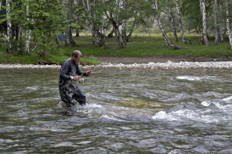 Visserij op de hengel van de bergrivier Visser die in de bergen vissen Forel visserij royalty-vrije stock afbeelding