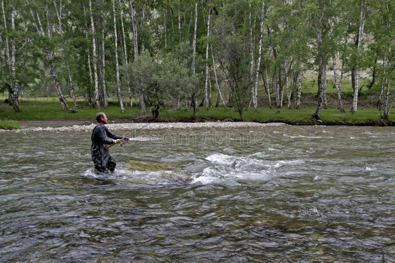 Visserij op de hengel van de bergrivier Visser die in de bergen vissen Forel visserij stock foto