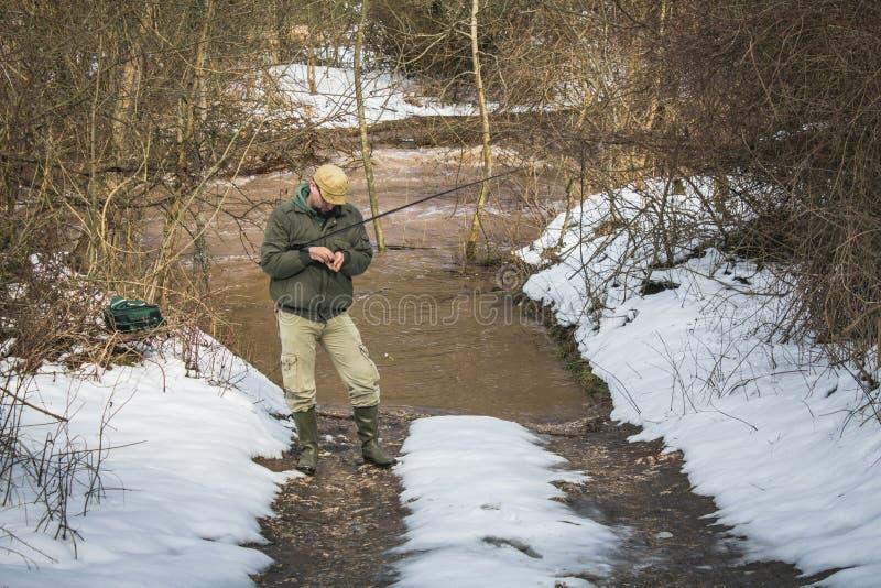 Visserij op de rivier in de winter De visser installeert de haak stock afbeeldingen