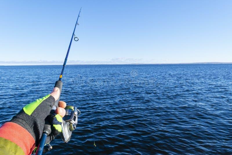 Visserij op het meer Handen van visser met hengel Lage diepte van gebied Hengel en handen van visser over meerwater spinning royalty-vrije stock foto