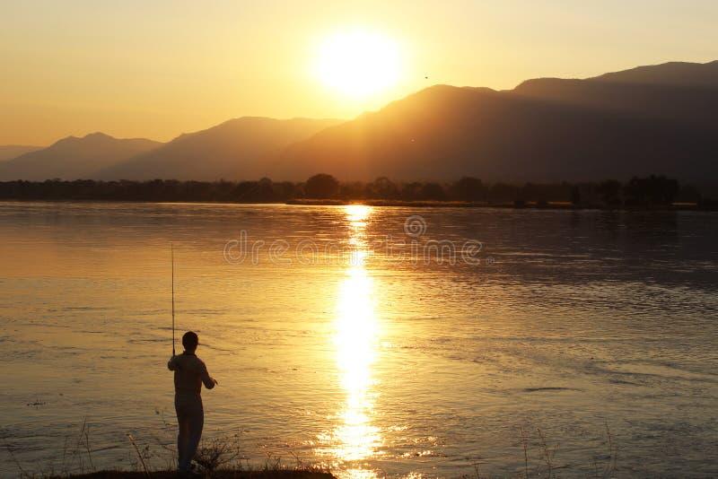 Visserij tijdens Zonsondergang stock afbeeldingen