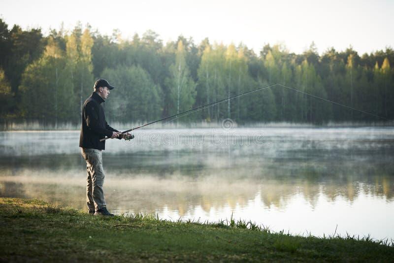 Visserij visser met het spinnen van staaf vroege ochtend royalty-vrije stock foto
