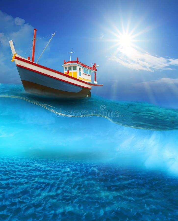 Visserijboot die op blauwe overzeese golf met zon drijven die op blauwe hemel glanzen stock foto