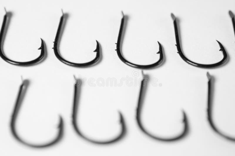 Visserijhaken met weerhaken op witte achtergrond op een rij stock fotografie