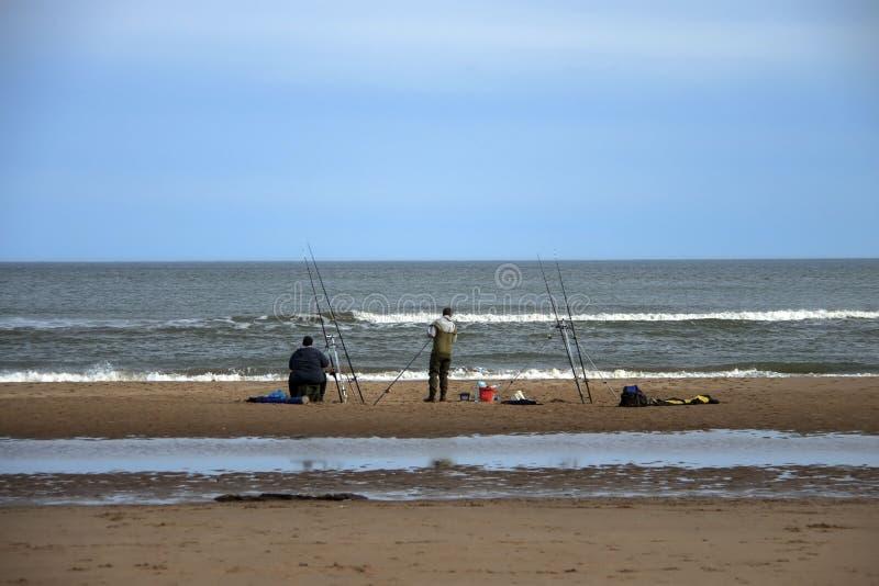 Vissers die door het overzees vissen St Cyrus, Aberdeenshire, Schotland stock afbeelding