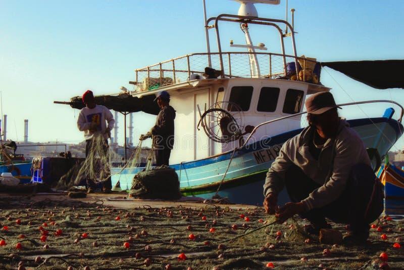 Vissers die en visnetten na de verse vangst van de dag verzamelen schoonmaken stock fotografie