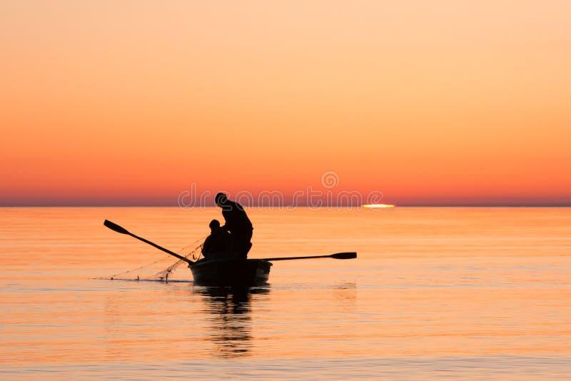 Vissers die visnet in overzees op zonsopgang trekken royalty-vrije stock foto
