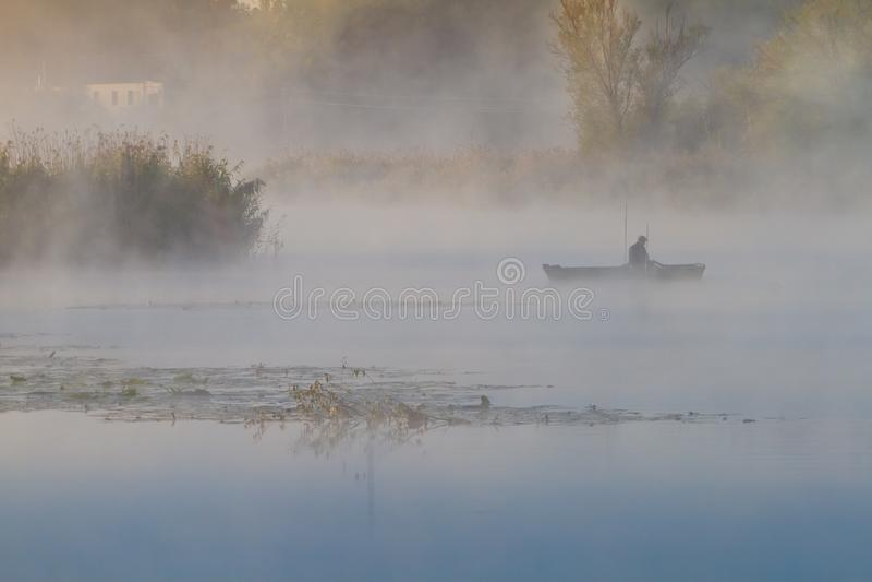 Vissers in een puntenboot die met staafjes vist, dikke mist bedekt nog steeds een rivier, bulrush, stok en wilgen groeien op een  stock foto