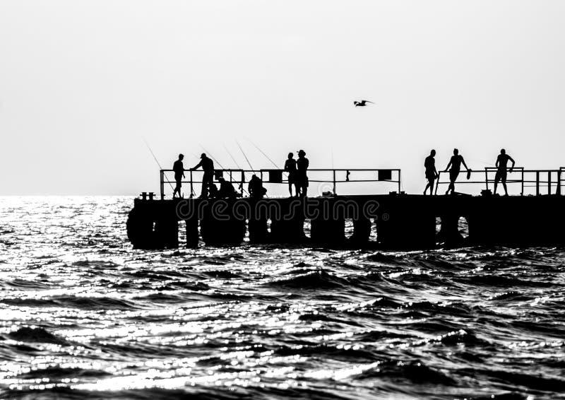 Vissers en vakantiegangers op een pijler stock foto's