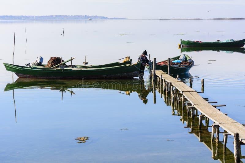 Vissers met hun oude boten, daling bij dageraad Het Zuidwesten van Sardinige royalty-vrije stock fotografie