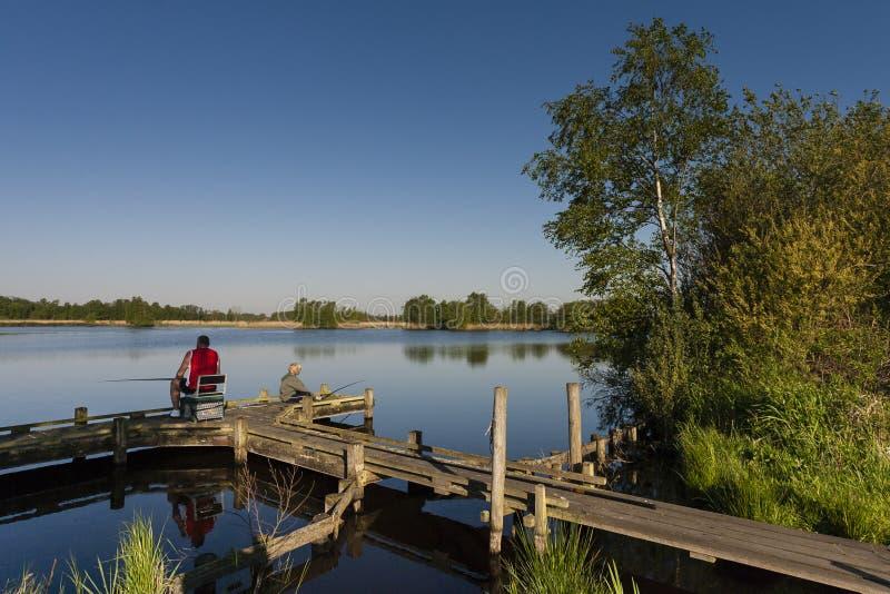 Vissers op steiger, Fishers at landing stage. Man en kind vissend vanaf steiger; Man and child fishing at landing stage stock photography