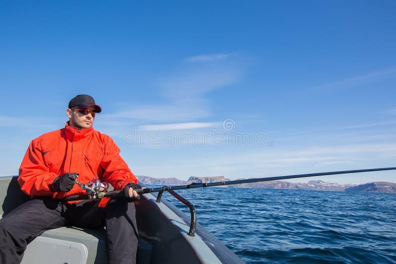 Vissersatleet die zonnebril met een spinnende staaf in van hem dragen royalty-vrije stock afbeeldingen