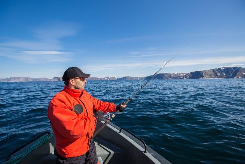 Vissersatleet met een hengel in zijn handen Een boot Overzees royalty-vrije stock fotografie