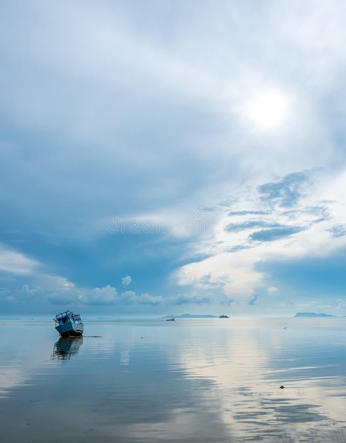 Vissersboot aan de grond over ondiep water stock fotografie