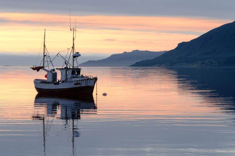 Vissersboot bij zonsondergang in de fjord stock fotografie