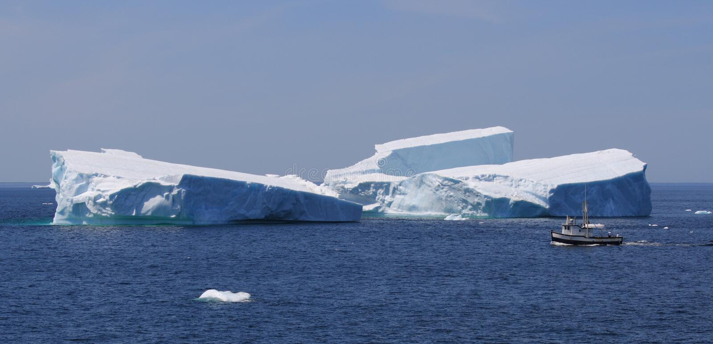 Vissersboot die Grote Ijsberg overgaat stock afbeeldingen