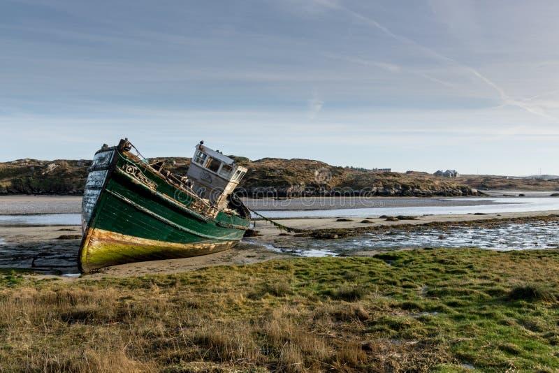 Vissersboot die op zijn kant rusten stock afbeelding