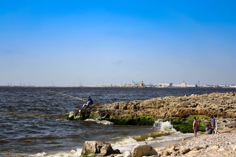 Vissersboot en een visser op het strand royalty-vrije stock fotografie