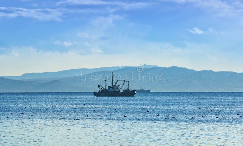 Vissersboot in grijze ochtend op Vreedzame oceaan van de kust van het Schiereiland van Kamchatka royalty-vrije stock foto's