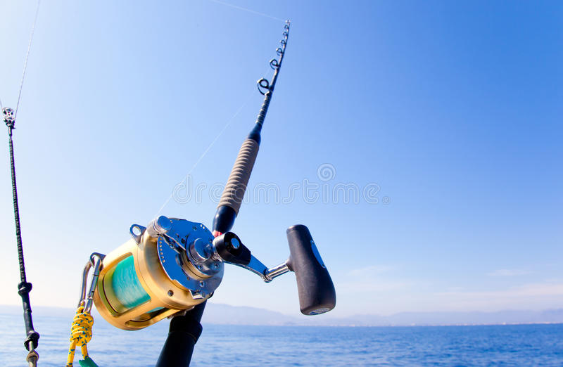 Vissersboot het met een sleeplijn vissen in oceaan met gouden spoel royalty-vrije stock afbeeldingen