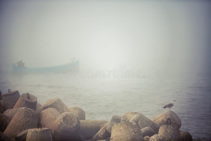 Vissersboot in het mistige overzees in een kalme vroege ochtend royalty-vrije stock foto's