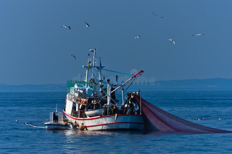 Vissersboot met nesten op zee voor berg Athos stock fotografie