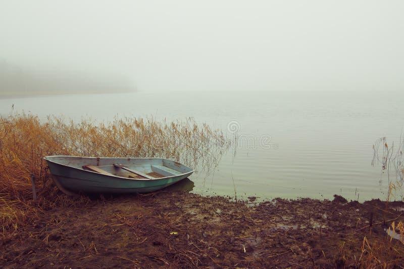 Vissersboot op het meer in de mist stock afbeeldingen