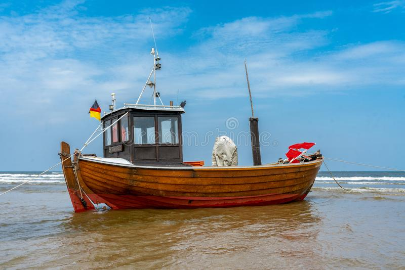 Vissersboot op strand at low tide stock foto's