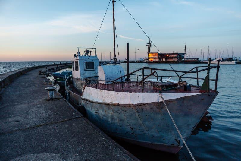 Vissersboten dichtbij de pijler in de haven van Nida litouwen stock foto's