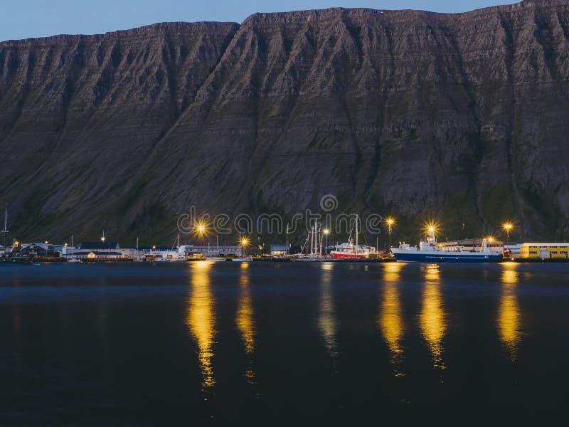 Vissersboten en donkere klip bij nacht in Husavik stock afbeeldingen