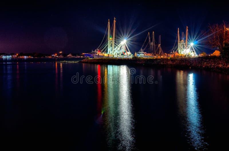 Vissersboten in jachthaven bij nacht stock foto