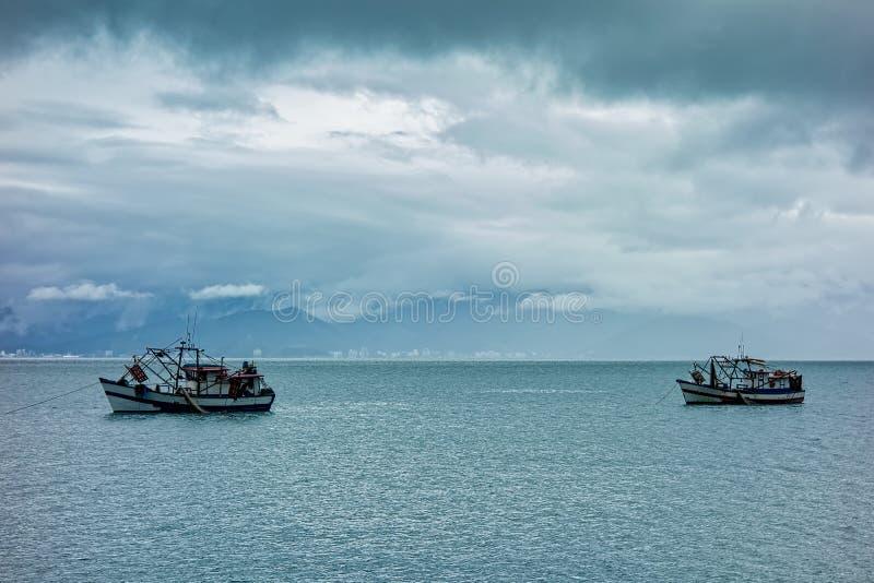 Vissersboten in Medio die kanaal tussen Sao Sebastiao en Ilhabela - São Paulo, Brazilië - van Ilhabela op een bewolkte dag wordt  royalty-vrije stock fotografie