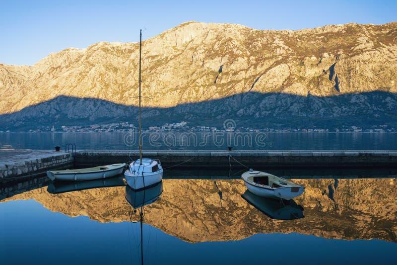 Vissersboten op het water in kleine haven Blauwe hemel en bergen die in het overzees wordt weerspiegeld Montenegro, Kotor-Baai royalty-vrije stock afbeelding