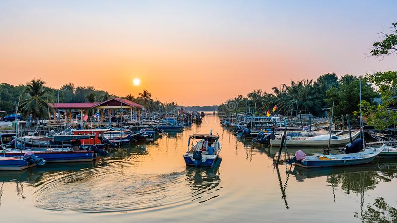 vissersmanoeuvre een boot aan het overzees tijdens schemer royalty-vrije stock foto