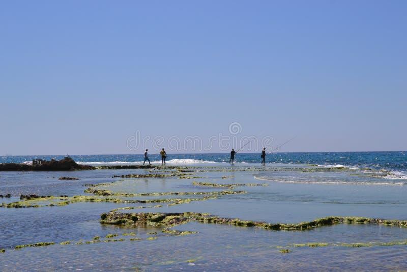 Vissersmensen die zich bij Kustlandschap bevinden van Caesarea Maritima, Middellandse Zee, Israël stock afbeeldingen