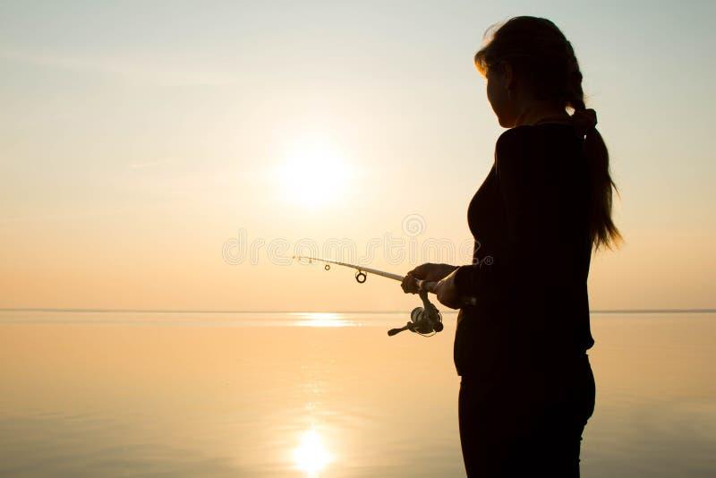 Visserssilhouet bij zonsondergang dichtbij het overzees stock afbeelding