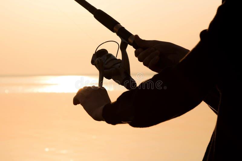 Visserssilhouet bij zonsondergang dichtbij het overzees royalty-vrije stock afbeeldingen