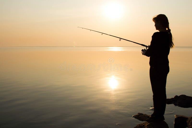 Visserssilhouet bij zonsondergang dichtbij het overzees royalty-vrije stock fotografie