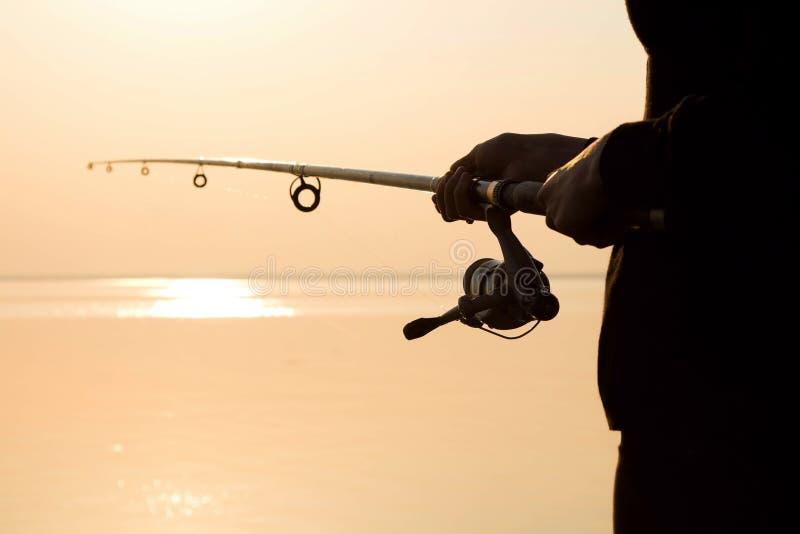 Visserssilhouet bij zonsondergang dichtbij het overzees met een hengel royalty-vrije stock afbeelding