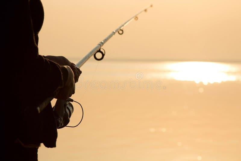 Visserssilhouet bij zonsondergang dichtbij het overzees met een hengel stock foto's