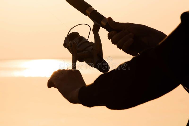 Visserssilhouet bij zonsondergang dichtbij het overzees met een hengel royalty-vrije stock foto's