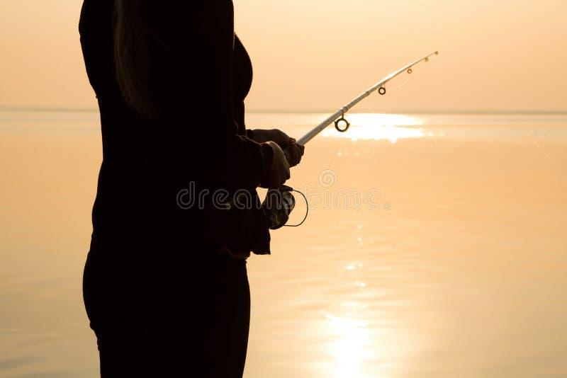 Visserssilhouet bij zonsondergang dichtbij het overzees met een hengel stock afbeelding