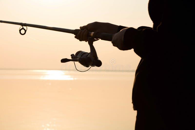 Visserssilhouet bij zonsondergang met een hengel royalty-vrije stock fotografie
