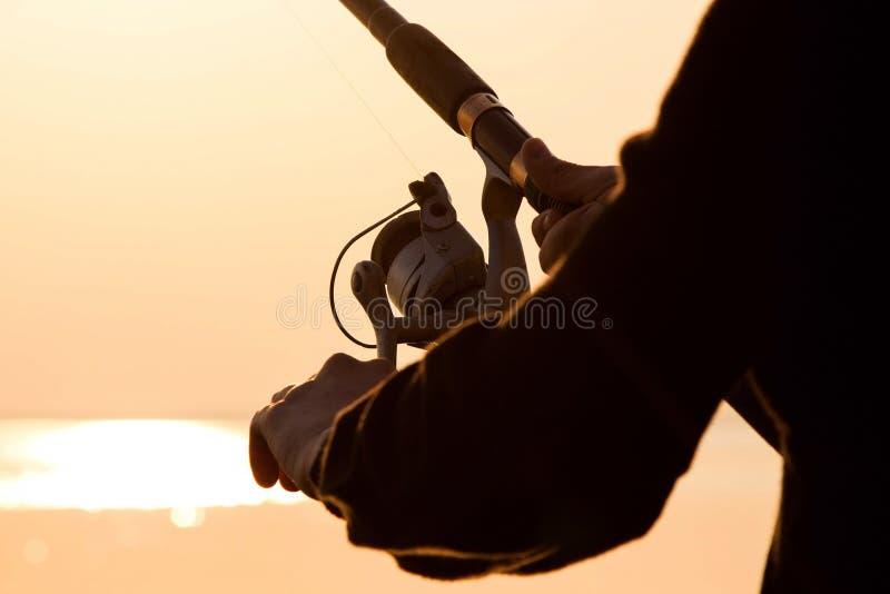 Visserssilhouet bij zonsondergang met een hengel stock foto