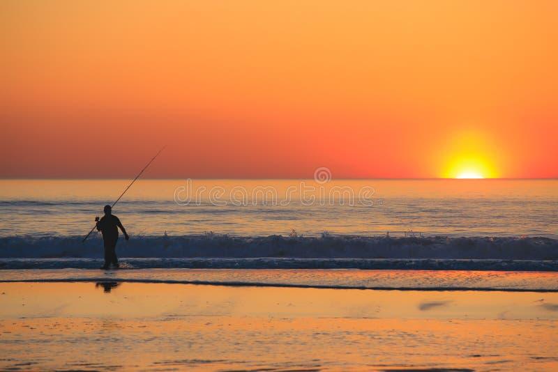 Visserssilhouet met staafzitting op overzees strand bij zonsondergang stock foto's